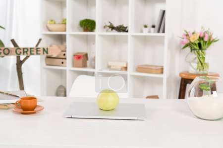 Photo for Workspace with apple on laptop near go green sign in modern office, environmental saving concept - Royalty Free Image
