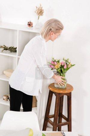 Foto de Mujer mirando flores en florero en oficina moderna - Imagen libre de derechos