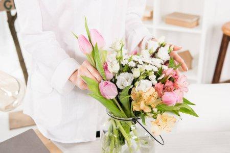 Photo pour Recadrée vue de femme près de fleurs dans un vase de verre - image libre de droit