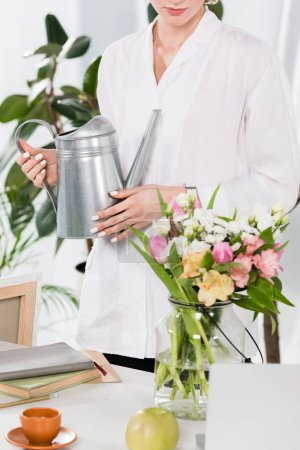 Photo pour Vue recadrée de femme d'affaires détenant arrosoir près de fleurs dans un vase, environnement économie concept - image libre de droit