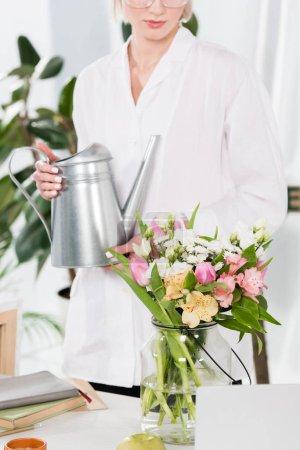 Photo pour Vue recadrée de femme tenant le bidon d'arrosage près de fleurs dans un vase, environnement économie concept - image libre de droit