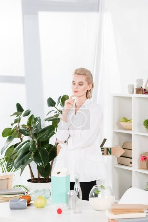 Photo for Pensive woman looking at desk with glass bottles cans and paper milk package in office, environmental saving concept - Royalty Free Image