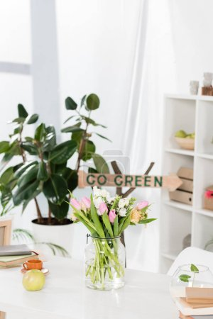 Photo for Selective focus of flowers in glass vase near wooden sign with go green lettering on background, environmental saving concept - Royalty Free Image