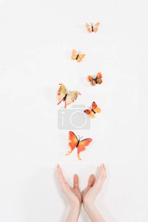 Photo for Cropped view of female hands near orange butterflies flying on white background, environmental saving concept - Royalty Free Image