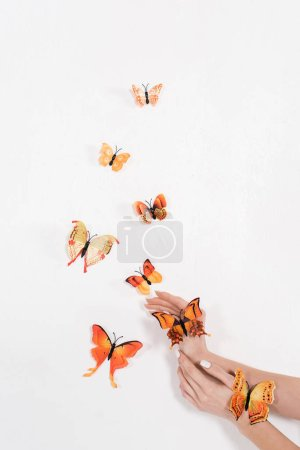 Photo pour Vue recadrée de la femme près de papillons orange sur fond blanc, concept d'économie d'environnement - image libre de droit