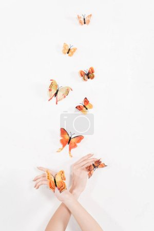 Photo for Cropped view of woman with crossed arms near orange butterflies flying on white background, environmental saving concept - Royalty Free Image