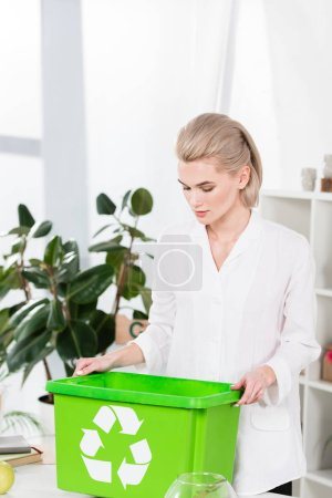 Photo for Beautiful businesswoman looking at green recycling box in office,  environmental saving concept - Royalty Free Image