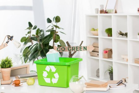 selective focus of green recycling box with paper milk package on desk with go green sign on background, environmental saving concept