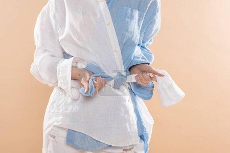 Foto de Vista recortada de mujer haga nudo estando eco ropa aislado en beige - Imagen libre de derechos
