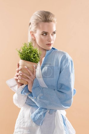 Photo for Woman holding pot with plant and standing in eco clothing isolated on beige, environmental saving concept - Royalty Free Image