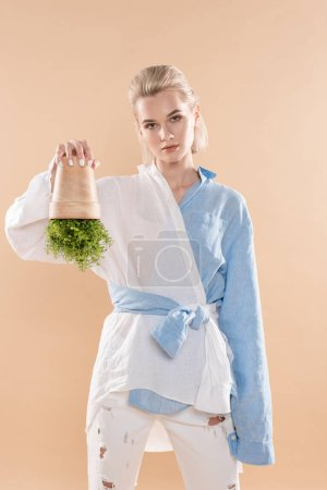Photo for Woman holding pot with plant upside down while standing in eco clothing isolated on beige, environmental saving concept - Royalty Free Image