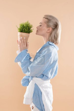 Photo for Profile of woman holding pot with plant and standing in eco clothing isolated on beige, environmental saving concept - Royalty Free Image