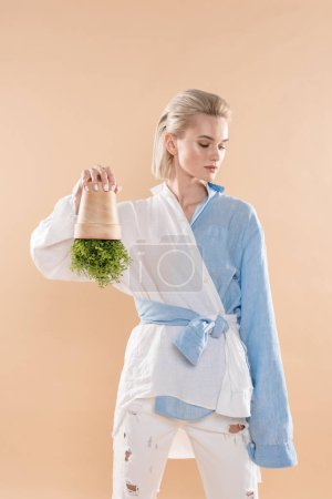 Photo for Young woman holding pot with plant upside down while standing in eco clothing isolated on beige, environmental saving concept - Royalty Free Image