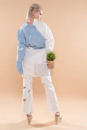 Photo pour Jeune fille tenant le pot avec la plante dans la main et en vêtements éco isolé sur concept salvateur beige, environnement - image libre de droit