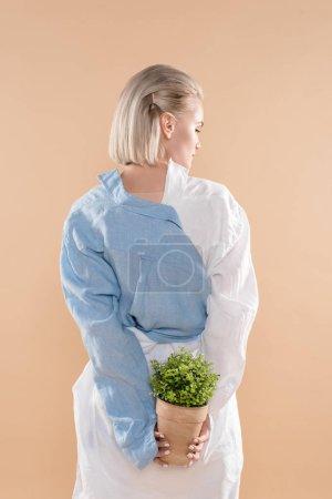 Foto de Joven mujer sosteniendo maceta con planta aislado en concepto de ahorro amarillento, medio ambiente - Imagen libre de derechos