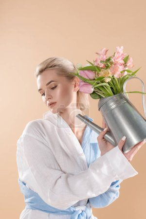 Photo for Woman holding watering can with flowers and standing in eco clothing isolated on beige, environmental saving concept - Royalty Free Image