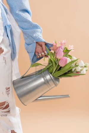 Photo for Cropped view of woman holding watering can with flowers and standing in eco clothing isolated on beige, environmental saving concept - Royalty Free Image