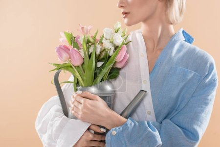 Photo pour Vue recadrée de jeune femme tenant arrosoir avec fleurs et permanent en eco vêtements isolés sur beige, environnement économie concept - image libre de droit
