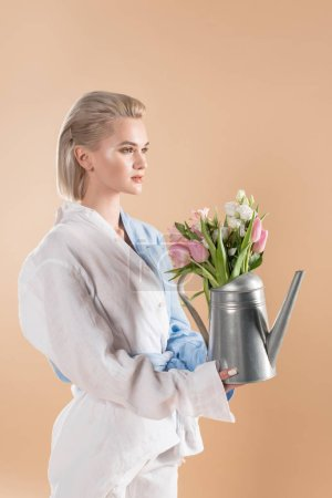 Photo for Beautiful woman holding watering can with flowers and standing in eco clothing isolated on beige, environmental saving concept - Royalty Free Image