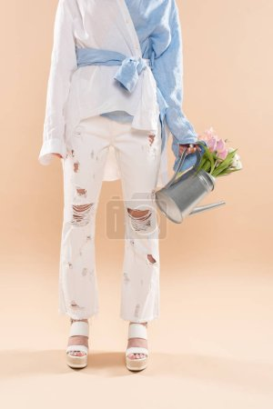 Photo for Cropped view of young woman holding watering can with flowers and standing in eco clothing isolated on beige, environmental saving concept - Royalty Free Image