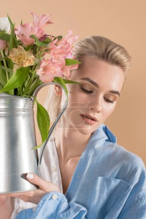 Photo for Attractive woman holding watering can with flowers and standing in eco clothing isolated on beige, environmental saving concept - Royalty Free Image