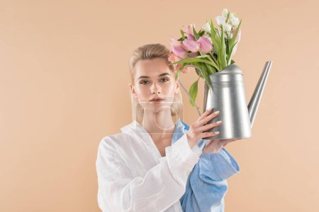 Photo for Beautiful girl holding watering can with flowers and standing in eco clothing isolated on beige, environmental saving concept - Royalty Free Image
