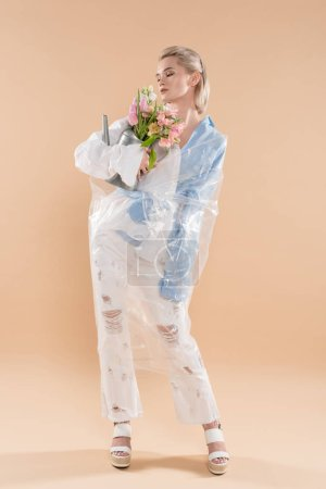 Foto de Attractive girl looking at flowers in watering can and standing in eco clothing wrapped in polyethylene isolated on beige, environmental saving concept - Imagen libre de derechos