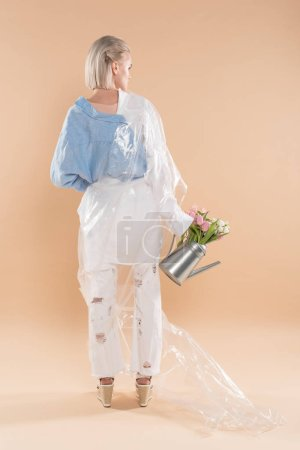 Foto de Girl holding watering can with flowers and standing in eco clothing wrapped in polyethylene isolated on beige, environmental saving concept - Imagen libre de derechos