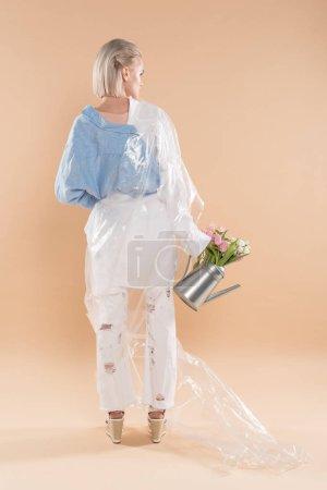 Foto de Niña sosteniendo regadera con flores y de pie en ropa eco envuelto en polietileno aislado en concepto de ahorro amarillento, medio ambiente - Imagen libre de derechos