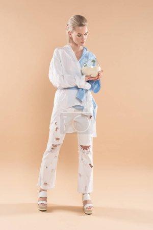 Photo pour Belle fille tenant le bocal à poissons avec sable et petite plante verte en se tenant debout dans vêtements éco sur fond beige, environnement économie concept - image libre de droit