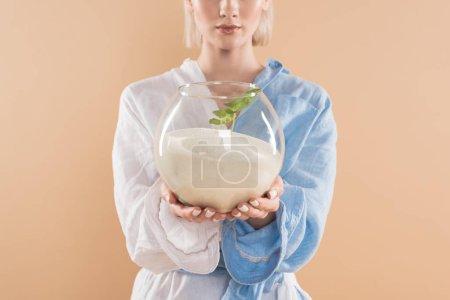 Photo pour Vue recadrée de femme tenant le bocal à poissons avec sable et petite plante verte en se tenant debout dans eco vêtements isolés sur beige, environnement économie concept - image libre de droit