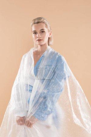 Foto de Mujer en ropa eco envuelto en polietileno aislado en beige, ambiental ahorro concepto - Imagen libre de derechos