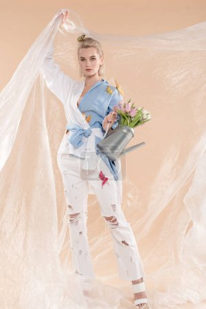 Photo pour Femme tenant en polyéthylène et arrosoir avec fleurs en se tenant debout en vêtements éco isolé sur beige, environnement économie concept - image libre de droit