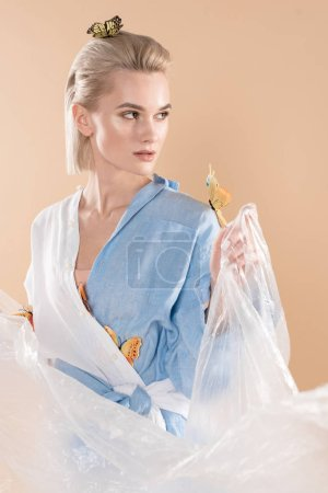 Photo for Attractive girl holding polyethylene while standing with butterflies on eco clothing isolated on beige, environmental saving concept - Royalty Free Image