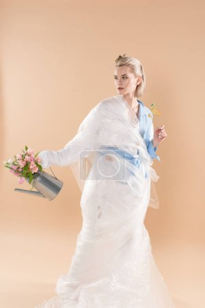 Foto de Beautiful girl wrapped in polyethylene holding watering can with flowers and standing in eco clothing isolated on beige, environmental saving concept - Imagen libre de derechos
