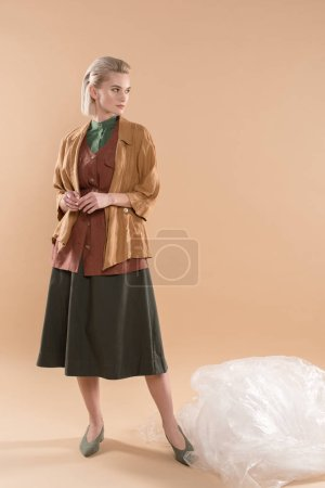 Photo for Attractive girl standing in eco clothing near polyethylene on beige background, environmental saving concept - Royalty Free Image