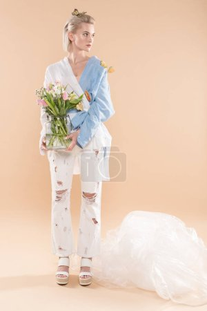 Photo for Beautiful yound woman standing with butterflies on eco clothing and holding glass vase with flowers on beige background, environmental saving concept - Royalty Free Image