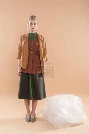 Foto de Chica rubia con eco permanente de ropa cerca de polietileno sobre fondo beige, ambiental ahorro concepto - Imagen libre de derechos
