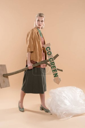 Foto de Chica rubia vestida con eco permanente de ropa cerca de polietileno y con cartel de madera con ir verde letras sobre fondo beige, concepto ahorro ambiental - Imagen libre de derechos