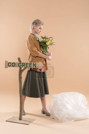 Photo for Blonde girl in eco clothing holding vase with flowers near sign with go green lettering on beige background, environmental saving concept - Royalty Free Image
