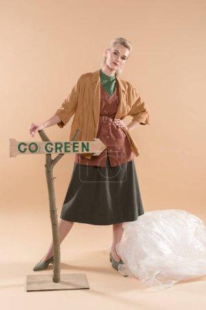 Foto de Muchacha atractiva en ropa ecológica cerca de polietileno y vaya cartel verde sobre fondo beige, ambiental ahorro concepto - Imagen libre de derechos