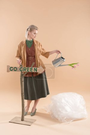Photo for Attractive girl in eco clothing holding watering can with flowers near sign with go green lettering on beige background, environmental saving concept - Royalty Free Image