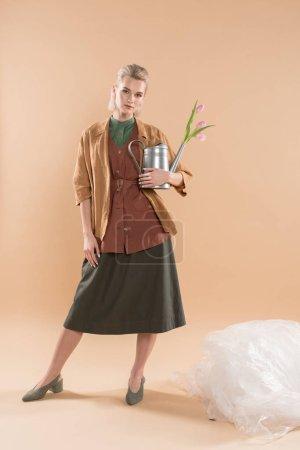 Photo pour Jolie fille en vêtements éco tenant arrosoir avec fleurs près de polyéthylène sur fond beige, environnement économie concept - image libre de droit