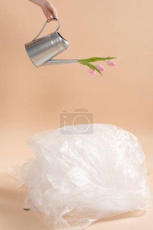Photo pour Vue recadrée de fille tenant arrosoir avec fleurs près de polyéthylène sur fond beige, environnement économie concept - image libre de droit
