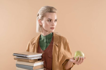 Foto de Attractive girl holding books and green apple while standing in eco clothing isolated on beige - Imagen libre de derechos