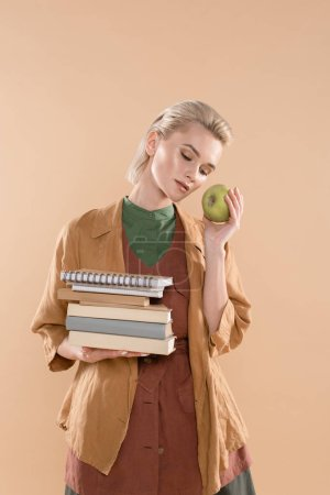 Photo pour Attractive young woman holding books and green apple while standing in eco clothing isolated on beige - image libre de droit