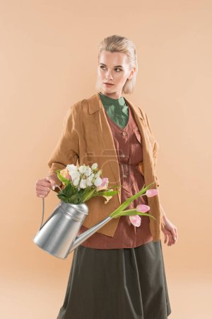 Photo for Blonde girl in eco clothing holding watering can with flowers isolated on beige, environmental saving concept - Royalty Free Image