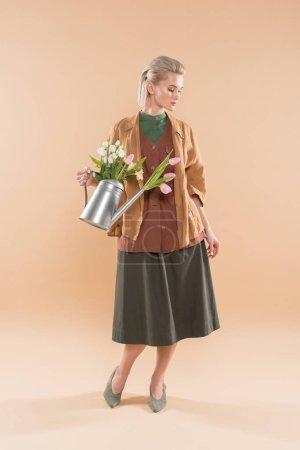 Foto de Chica atractiva en la ropa eco holding regadera con flores sobre fondo beige, ambiental ahorro concepto - Imagen libre de derechos
