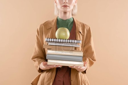 Foto de Cropped view of young woman holding books and green apple while standing in eco clothing isolated on beige - Imagen libre de derechos