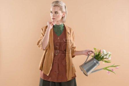 Photo pour Songeuse fille vêtements éco tenant le bidon d'arrosage avec des fleurs isolées sur fond beige, environnement économie concept - image libre de droit